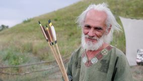 Ein alter Mann im ethnischen Kostüm steht auf einem Gebiet und zeigt Pfeile stock video footage