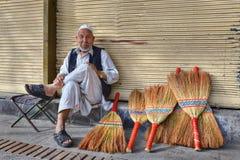 Ein alter Mann verkauft Besen auf einer Stadtstraße Lizenzfreie Stockbilder