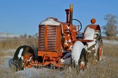 Ein alter orange Traktor sitzt im Schnee lizenzfreies stockbild