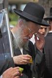 Ein alter orthodoxer Jude im schwarzen Hut wählt Zitrusfrucht aus Lizenzfreie Stockfotografie
