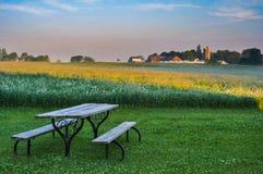 Ein alter Picknicktisch in einem Rasen, der in Richtung eines Bauernhofes über einem Luzernefeld blickt lizenzfreies stockfoto