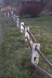 Ein alter roter Zaun an der Landstraße ein nebeligen Morgen Stockbild
