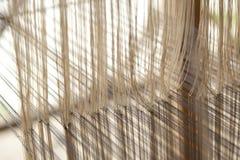 Ein alter spinnender Webstuhl und ein Thread des Garns Stockbilder