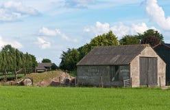 Ein alter Stall mit hölzernen Türen in einer holländischen Landschaft Stockbilder