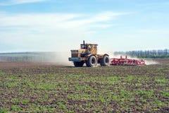Ein alter Traktor schleppt eine moderne Gesamtheit für den Ackerbau, der die Feldoberfläche planiert Stockfotografie