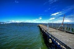 Ein alter verwitterter Pier mit einem Kettengliedzaun HDR Stockfotos