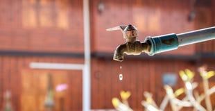 Ein alter Wasserhahn in droping Wasser des ländlichen Dorfs Lizenzfreie Stockfotos