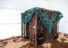 Ein altes Akkordeon bedeckt mit einer Wolldecke Das Eigentum von Zeiten lizenzfreie stockfotografie