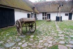 Ein altes Bauernhofyard und -häuser Stockfotografie