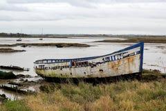 Ein altes Boot auf dem Sand auf der Seite von einer Mündung Stockfotografie