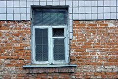Ein altes Fenster mit einem Gitter auf der Backsteinmauer des Hauses Lizenzfreie Stockbilder