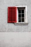 Ein altes Fenster mit einem roten Fensterladen und einer weißen Wand Lizenzfreies Stockbild