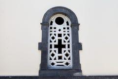 Ein altes Gefängnisfenster mit einem Steinwandgrill mit einem Quersymbol des Glaubens stockfoto
