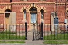 Ein altes Gefängnisgebäude mit einem Eisenzaun lizenzfreies stockbild