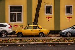 Ein altes gelbes russisches Auto parkte zwischen zwei Neuwagen Stockbild