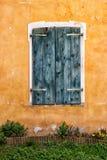 Ein altes hölzernes Fenster und eine gelbe Wand Lizenzfreie Stockfotos