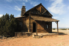 Ein altes hölzernes Gebäude sitzt auf dem Grasland des ländlichen New Mexiko Stockbild