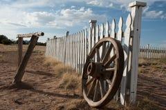 Ein altes hölzernes Lastwagenrad lehnt sich an einem Bretterzaun Stockfotografie