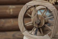 Ein altes hölzernes Rad auf dem Hintergrund eines alten Blockhauses stockfoto