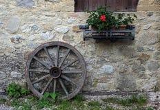 Ein altes hölzernes Rad, das an einer Steinwand sich lehnt Stockfoto