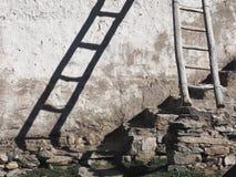 Ein altes hölzernes Treppenhaus lehnt sich an einer weißen Wand, ein Schatten von den Treppenfällen auf die Wand, Steine im Kelle Lizenzfreie Stockfotos