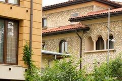 Ein altes Haus nahe bei einem modernen Gebäude Lizenzfreie Stockfotografie