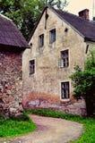 Ein altes Haus und eine grungy Straße in Lettland lizenzfreie stockbilder