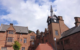 Ein altes Herrenhaus und ein Glockenturm Lizenzfreie Stockbilder