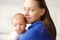 Ein altes neugeborenes Baby des Monats mit Mutter Stockbild