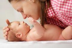 Ein altes neugeborenes Baby des Monats mit Mutter Stockbilder