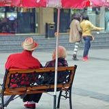 Ein altes Paar, das auf einem Stuhl auf einer verkehrsreichen Straße stillsteht Stockbild