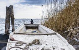 Ein altes Plastikfischerboot durch den See Lizenzfreies Stockbild