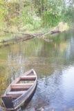 Ein altes Reihenboot durch einen Pier auf einem ruhigen See Es ist früher Morgen und alles ist ruhig lizenzfreie stockfotos