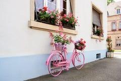 Ein altes rosa Fahrrad als Blumenstand an der Hausmauer in Frankreich Lizenzfreie Stockbilder