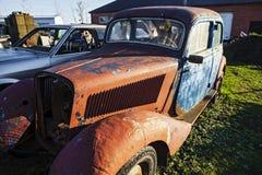 Ein altes rostiges Auto in einem Autodump stockfotos