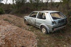 Ein altes rostiges Autowrack, das auf einem Feld steht Stockfoto