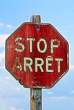 Ein altes Stoppschild auf französisches und englisch gegen einen blauen Himmel stockbilder