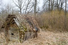 Ein altes verfallen wenigem hölzernem verlassenem ruiniertem gebrochenem Dorfhaus von Strahlen, von Klotz und von Stöcken in der  stockfotografie