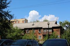 Ein altes verfallenes Haus auf dem Hintergrund eines neuen Hauses Lizenzfreies Stockbild