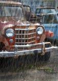 Ein altes verrostendes rotes Auto im Regen stockfotos