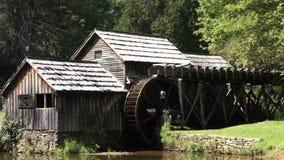 Ein altes Wasserrad, das an einer konservierten Mahlgutmühle sich dreht
