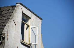 Ein altes weißes niederländisches Gebäudedach mit offenen Fensterläden und einem weißen f Stockfotos