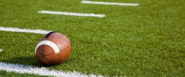 Ein amerikanischer Fußball auf Feld Stockfotos
