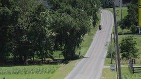 Ein amisches Pferd und ein verwanztes Reiten entlang der Straße auf der Landschaft stock video