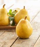 Ein Ananasschnitt geschnitten zur Hälfte Frische organische Birnen auf altem Holz Lizenzfreie Stockbilder