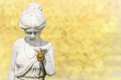 Ein antikes Goldmedaillon wird dargestellt von der Steinstatuenfrau stockbild