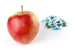 Ein Apple und ein Stapel der Medikation-Pillen Lizenzfreie Stockfotografie