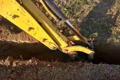 Ein Arbeitsbagger, der einen Graben für die Grundlage eines Gebäudes gräbt stockfotografie