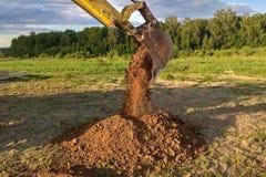Ein Arbeitsbagger, der einen Graben für die Grundlage eines Gebäudes gräbt lizenzfreie stockfotos