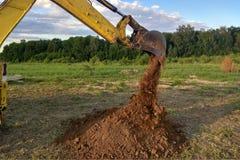 Ein Arbeitsbagger, der einen Graben für die Grundlage eines Gebäudes gräbt lizenzfreie stockfotografie